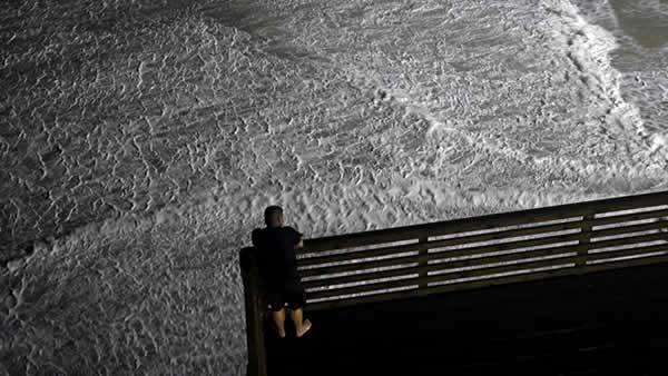 Waves surround an ocean-front hotel deck as a man looks on while Hurricane Earl passes offshore in Nags Head, N.C., Friday, Sept. 3, 2010.