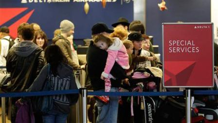 Travelers wait to check-in at a Delta Air Lines counter at Seattle-Tacoma International Airport, Monday, Dec. 27, 2010, in Seattle. Delta and other airlines had flights to and from the New York area cancelled or otherwise affected by winter weather.