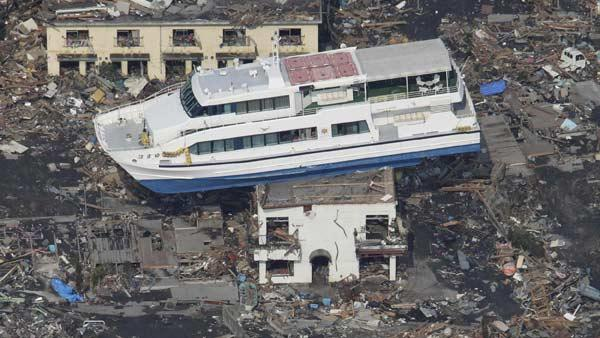 A ferry stranded on a building is seen in Otsuchi, Iwate Prefecture, northern Japan, Sunday, March 13, 2011, two days after a powerful earthquake-triggered tsunami hit the country's east coast. (AP Photo/The Yomiuri Shimbun)