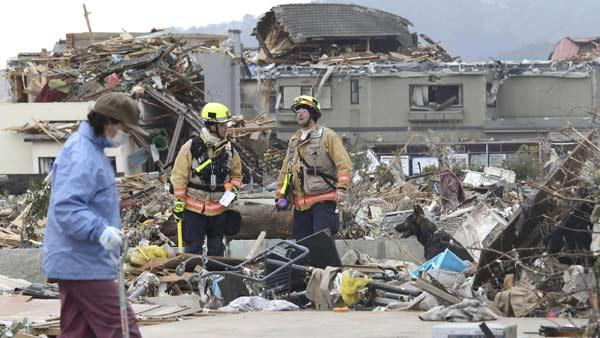 A tsunami survivor, left, looking for belongings from where her house was standing walks by U.S. rescue team members with a sniff dog working in debris in Ofunato in Iwate Prefecture (state), northeastern Japan, Tuesday, March 15, 2011.