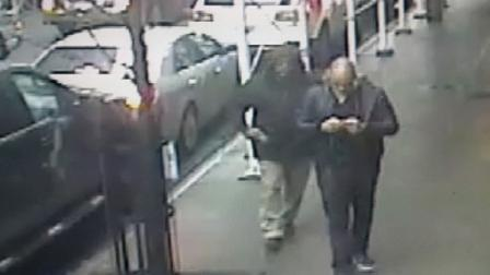 This still image made from a video provided by the New York City Police Department shows the gunman, left, behind Brandon Lincoln Woodard