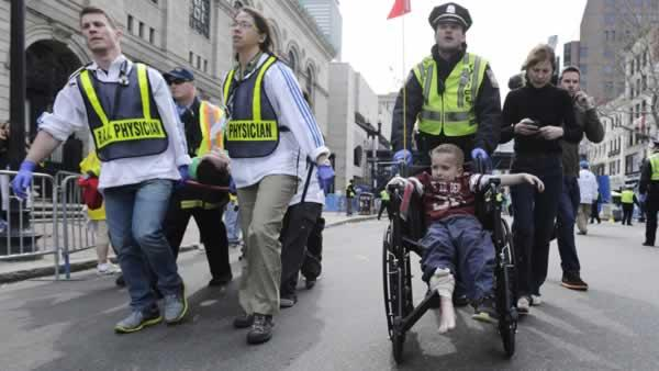 A Boston police officer wheels in injured boy following an explosion during the 2013 Boston Marathon in Boston, Monday, April 15, 2013. (AP Photo/Charles Krupa)