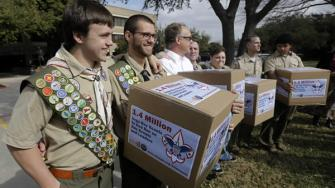 File photo James Oliver, left, hugs his brother and fellow Eagle Scout, Will Oliver, who is gay, as Will and other supporters carry four boxes filled with a petition in front of the Boy Scouts of America headquarters, in Dallas, Texas