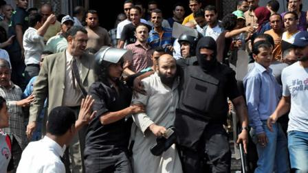 Egyptians security forces escort an Islamist supporter of the Muslim Brotherhood out of the al-Fatah mosque, after hundreds of Islamist protesters barricaded themselves inside the mosque overnight