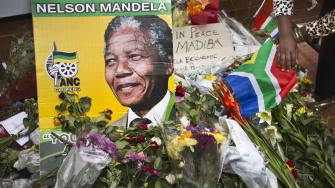 Flowers, posters, and messages left by mourners lie in front of Nelson Mandelas old house in Soweto, Johannesburg, South Africa, Saturday, Dec. 7, 2013