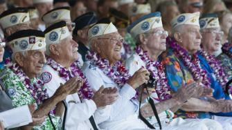 Pearl Harbor survivors watch a vintage WWII airplane fly over Pearl Harbor at the ceremony commemorating the 72nd anniversary of the attack on Pearl Harbor, Saturday, Dec. 7, 2013