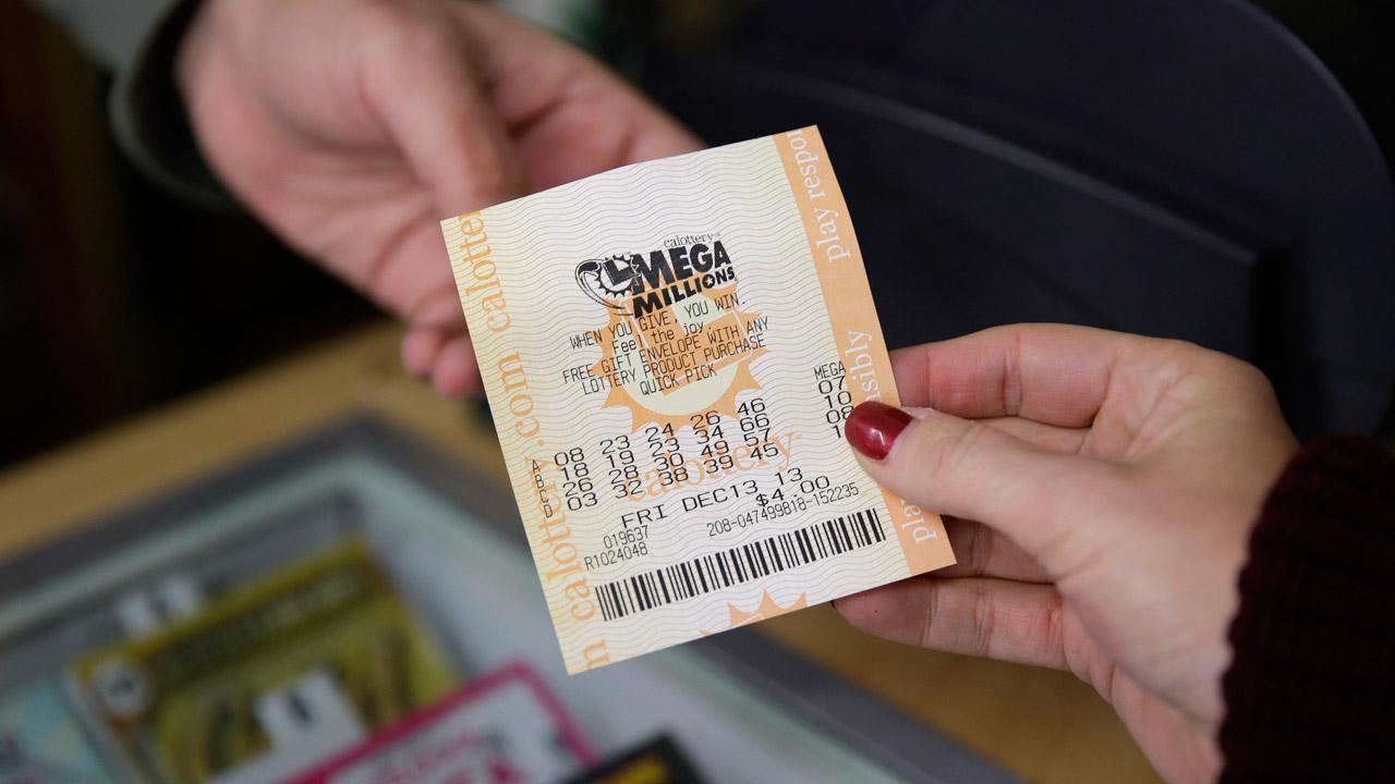 A woman purchases a Mega Millions lottery ticket at a Financial District liquor store Thursday, Dec. 12, 2013, in San Francisco.