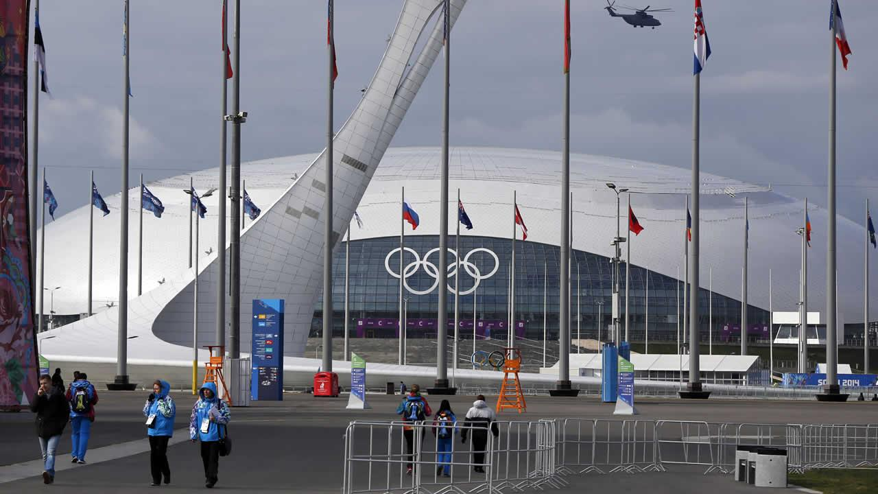 A military helicopter flies over Olympic Park, passing the Olympic Cauldron, center, and the Bolshoy Ice Dome, rear, ahead of the 2014 Winter Olympics, Wednesday, Feb. 5, 2014, in Sochi, Russia