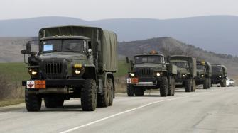 A convoy of military vehicles bearing no license plates travels on the road from Feodosia to Simferopol in the Crimea, Ukraine, Saturday, March 8, 2014