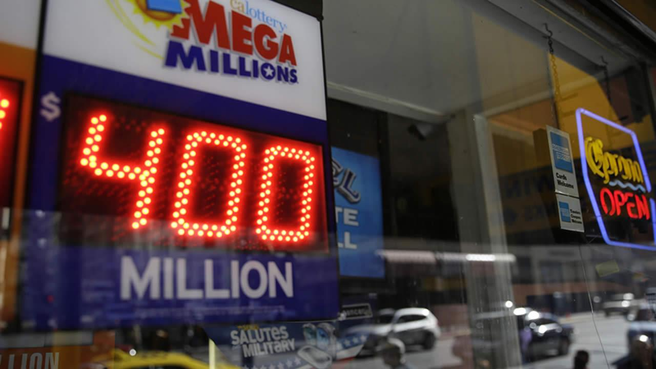 File-This Dec. 12, 2013 file photo shows a sign displaying the current Mega Millions jackpot at a Financial District liquor store in San Francisco.