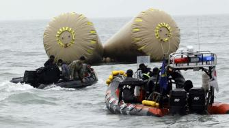 South Korean rescue members search passengers believed to have been trapped in the sunken ferry Sewol near the buoys which were installed to mark the area in the water off the southern coast near Jindo, south of Seoul, South Korea