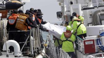 South Korean Coast Guard police officers on a boat carry the body of a passenger believed to have been trapped in the sunken ferry Sewol in the water off the southern coast near Jindo, south of Seoul, South Korea, Sunday, April 20, 2014