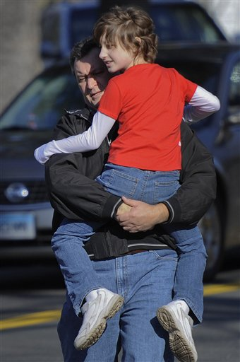 A man carries a child away from the area of a shooting at the Sandy Hook Elementary School in Newtown, Conn., about 60 miles &#40;96 kilometers&#41; northeast of New York City, Friday, Dec. 14, 2012. A man opened fire Friday inside two classrooms at the school where his mother worked as a teacher, killing 26 people, including 20 children. The killer, armed with two handguns, committed suicide at the school and another person was found dead at a second scene, bringing the toll to 28, authorities said. A law enforcement official identified the gunman as 20-year-old Adam Lanza. <span class=meta>(AP Photo&#47;Jessica Hill)</span>