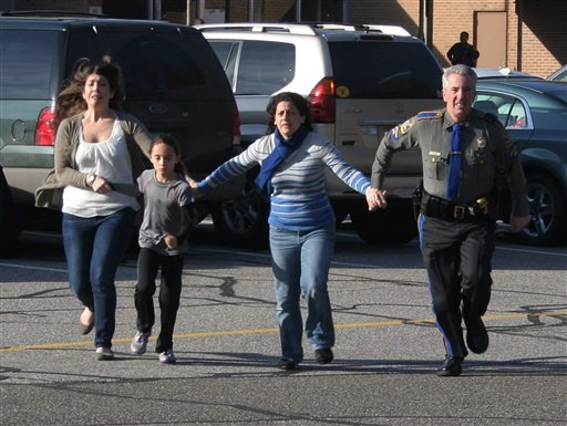 In this photo provided by the Newtown Bee, a police officer leads two women and a child from Sandy Hook Elementary School in Newtown, Conn., where a gunman opened fire, killing 26 people, including 20 children, Friday, Dec. 14, 2012.  <span class=meta>(AP Photo&#47;Newtown Bee, Shannon Hicks)</span>