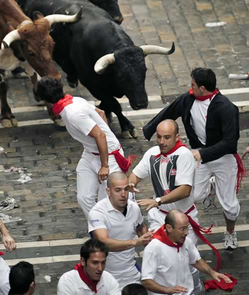"<div class=""meta image-caption""><div class=""origin-logo origin-image ""><span></span></div><span class=""caption-text""> Revelers run next to Torrestrella ranch fighting bulls during the running of the bulls at the San Fermin fiestas on Thursday, July 7, 2011, in Pamplona, Spain. (AP Photo/Daniel Ochoa de Olza) </span></div>"