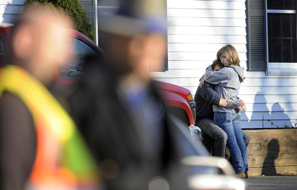 People embrace at a firehouse staging area for family around near the scene of a shooting at the Sandy Hook Elementary School in Newtown, Conn., about 60 miles &#40;96 kilometers&#41; northeast of New York City, Friday, Dec. 14, 2012. An official with knowledge of Friday&#39;s shooting said 27 people were dead, including 18 children. <span class=meta>(AP Photo&#47;Jessica Hill)</span>
