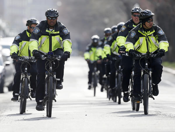 Boston police on bicycles patrol on Commonwealth Avenue following the explosions at the finish line of the Boston Marathon in Boston, Monday, April 15, 2013. Two bombs exploded at the Boston Marathon finish line Monday killing two people and injuring dozens. (AP Photo/Michael Dwyer)
