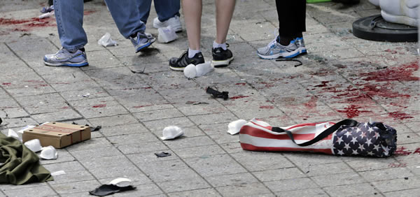 Blood from victims covers the sidewalk on Boylston Street, at the site of an explosion during the 2013 Boston Marathon in Boston, Monday, April 15, 2013. (AP Photo/Charles Krupa)