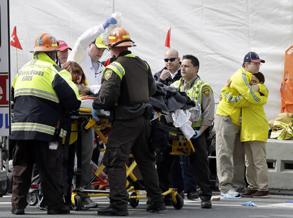 Two Boston Marathon volunteers hug each other, at right, as an injured person is loaded into an ambulance in the aftermath of two blasts which exploded at the Boston Marathon in Boston
