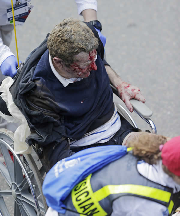 Medical workers aid an injured man at the finish line of the 2013 Boston Marathon following an explosion there Monday, April 15, 2013 in Boston. (AP Photo/Charles Krupa)