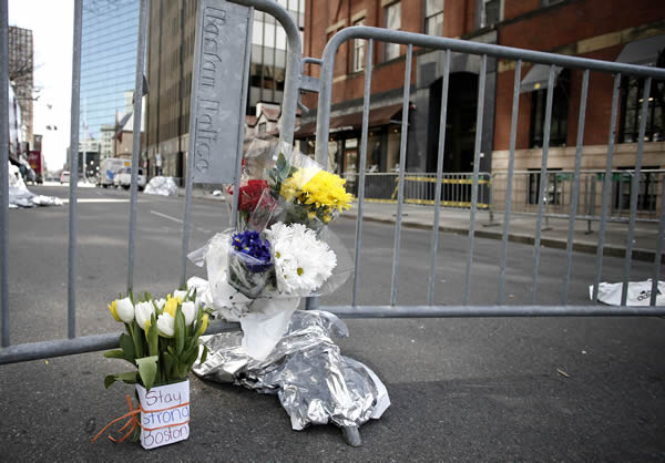 Flowers sit at a police barrier near the finish line of the Boston Marathon in Boston Tuesday, April 16, 2013. The bombs that ripped through the crowd at the Boston Marathon, killing at least three people and wounding more than 170, were fashioned out of pressure cookers and packed with shards of metal, nails and ball bearings to inflict maximum carnage, a person briefed on the investigation said Tuesday. (AP Photo/Winslow Townson)