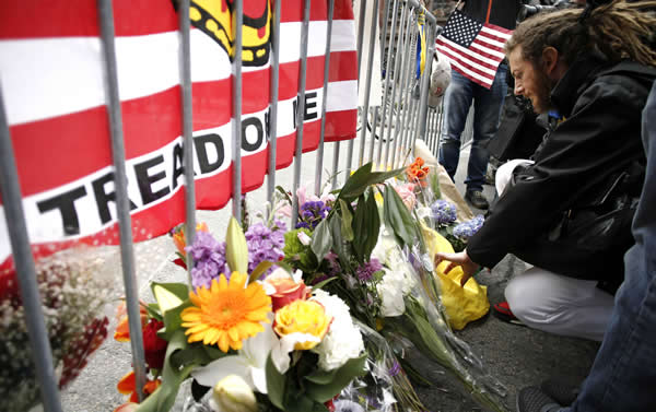 A mourner places a note with flowers at a police barricade near the finish line of the Boston Marathon in Boston Tuesday, April 16, 2013. The bombs that ripped through the crowd at the Boston Marathon, killing three people and wounding more than 170, were fashioned out of pressure cookers and packed with metal shards, nails and ball bearings to inflict maximum carnage, a person briefed on the investigation said Tuesday. (AP Photo/Winslow Townson)