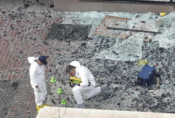 Two men in hazardous materials suits put numbers on the shattered glass and debris as they investigate the scene at the first bombing on Boylston Street in Boston Tuesday, April 16, 2013
