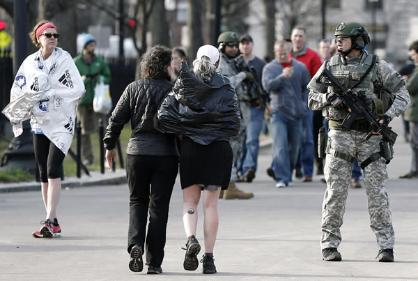As Boston Marathon runners walk by, SWAT team members stand guard near the finish line in Boston Monday, April 15, 2013. Two explosions shattered the euphoria of the Boston Marathon finish line on Monday, sending authorities out on the course to carry off the injured while the stragglers were rerouted away from the smoking site of the blasts. ( (AP Photo/Winslow Townson)