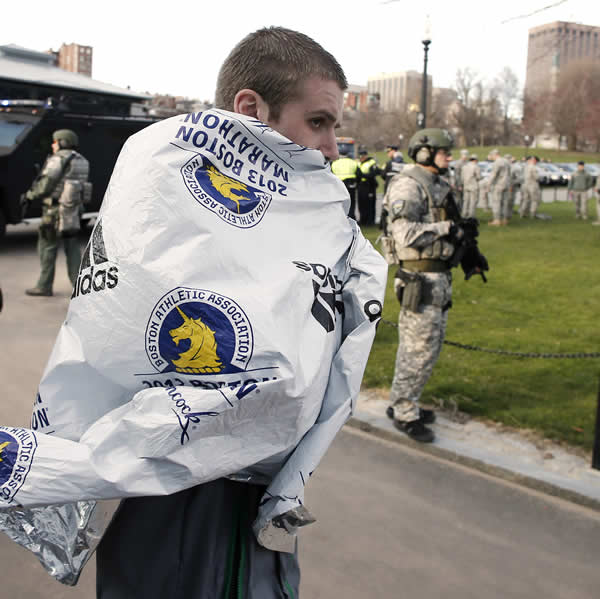 "<div class=""meta ""><span class=""caption-text "">Boston Marathon runner Russell Clifford of Marlborough, Mass. walks past SWAT officers near the finish line of the Boston Marathon in Boston Monday, April 15, 2013. Two explosions shattered the euphoria of the Boston Marathon finish line on Monday, sending authorities out on the course to carry off the injured while the stragglers were rerouted away from the smoking site of the blasts (AP Photo/Winslow Townson)</span></div>"