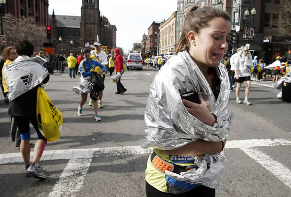 An unidentified Boston Marathon runner leaves the course crying near Copley Square following an explosion in Boston Monday, April 15, 2013. (AP Photo/Winslow Townson)