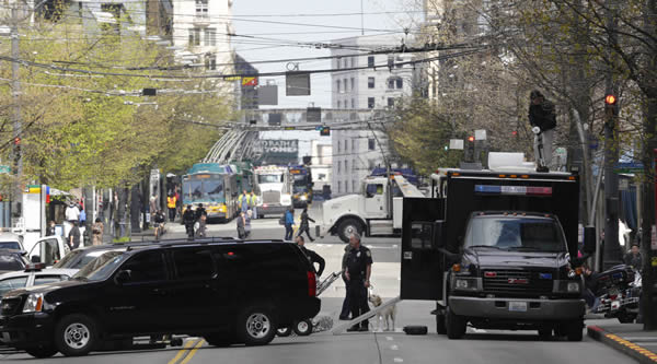 Seattle Police Dept. vehicles block off a street in while remote controlled vehicles are used to examine a suspicious backpack in downtown Seattle, Tuesday, April 16, 2013. The backpack was found to be harmless, but in light of Monday's explosions at the Boston Marathon, authorities in Seattle and other cities increased security patrols and heightened the level of alertness for any possible threat to public safety. (AP Photo/Ted S. Warren)