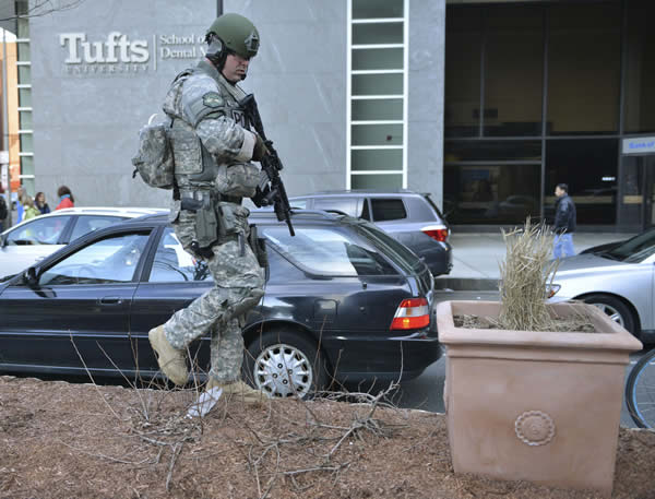 A S.W.A.T officer checks planters on a median in a road next to Tufts Medical Center following an explosion after the Boston Marathon in Boston, Monday, April 15, 2013. (AP Photo/Josh Reynolds)