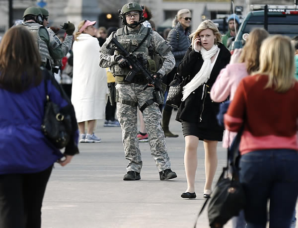 A SWAT team member stands guard near the finish line of the Boston Marathon in Boston Monday, April 15, 2013. Two explosions shattered the euphoria of the Boston Marathon finish line on Monday, sending authorities out on the course to carry off the injured while the stragglers were rerouted away from the smoking site of the blasts. (AP Photo/Winslow Townson)