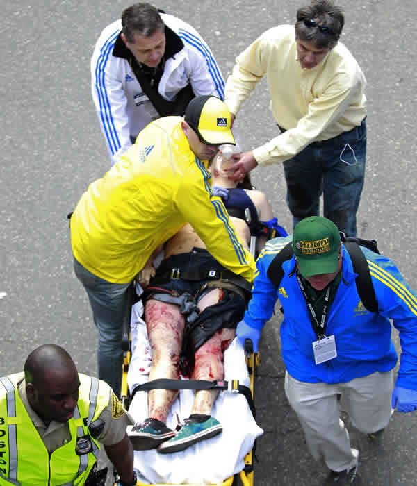 Medical workers aid an injured man at the finish line of the 2013 Boston Marathon following an explosion in Boston, Monday, April 15, 2013. (AP Photo/Charles Krupa)