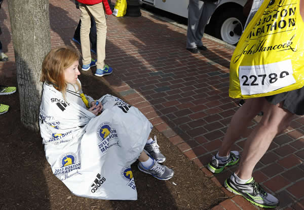 A runner who did not wish to be identified sits alone following an explosion at the finish line of the Boston Marathon in Boston, Monday, April 15, 2013. (AP Photo/Michael Dwyer)