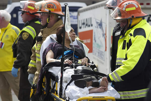 "<div class=""meta ""><span class=""caption-text "">Emergency responders aid a woman on a stretcher who was injured in a bomb blast near the finish line of the Boston Marathon Monday, April 15, 2013 in Boston. Two bombs exploded in the packed streets near the finish line of the marathon on Monday, killing at least two people and injuring more than 80, authorities said. (AP Photo/Jeremy Pavia)</span></div>"