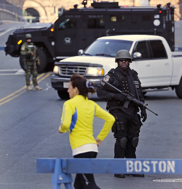 "<div class=""meta image-caption""><div class=""origin-logo origin-image ""><span></span></div><span class=""caption-text"">A runner passes a police officer dressed in tactical gear, who blocks a road leading to the Boston Marathon route, the morning after explosions killed three and injured more than 140 in Boston, Tuesday, April 16, 2013. The bombs that blew up seconds apart at the finish line of one of the world's most storied races left the streets spattered with blood and glass, and gaping questions of who chose to attack at the Boston Marathon and why. (AP Photo/Charles Krupa)</span></div>"