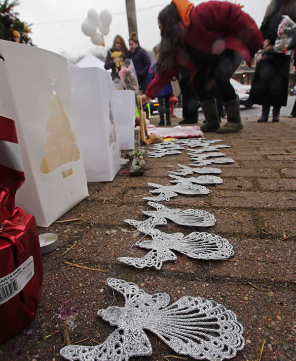 "<div class=""meta image-caption""><div class=""origin-logo origin-image ""><span></span></div><span class=""caption-text"">A woman lays flowers at the site of a makeshift memorial for school shooting victims at the village of Sandy Hook in Newtown, Conn., Sunday, Dec. 16, 2012. A gunman opened fire at Sandy Hook Elementary School in the town, killing 26 people, including 20 children before killing himself on Friday. (AP Photo/Charles Krupa)</span></div>"