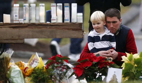 "<div class=""meta ""><span class=""caption-text "">A man holds a child while paying respects to shooting victims at a makeshift memorial outside of St. Rose of Lima Roman Catholic Church, Sunday, Dec. 16, 2012, in Newtown, Conn. On Friday, a gunman killed his mother at their home and then opened fire inside the Sandy Hook Elementary School in Newtown, killing 26 people, including 20 children.(AP Photo/Julio Cortez)</span></div>"