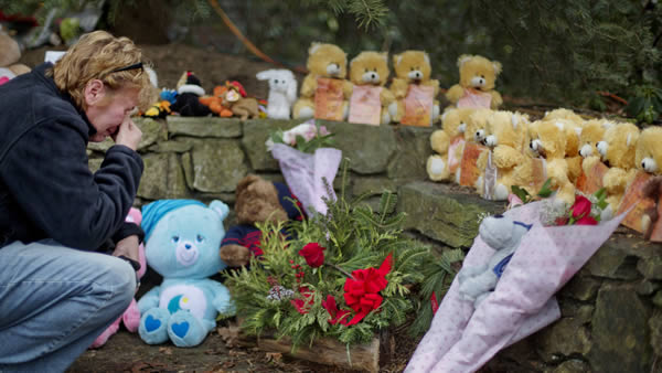 "<div class=""meta image-caption""><div class=""origin-logo origin-image ""><span></span></div><span class=""caption-text"">Cheryl Girardi, of Middletown, Conn., kneels beside 26 teddy bears, each representing a victim of the Sandy Hook Elementary School shooting, at a sidewalk memorial, Sunday, Dec. 16, 2012, in Newtown, Conn. A gunman walked into Sandy Hook Elementary School in Newtown Friday and opened fire, killing 26 people, including 20 children.(AP Photo/David Goldman)</span></div>"