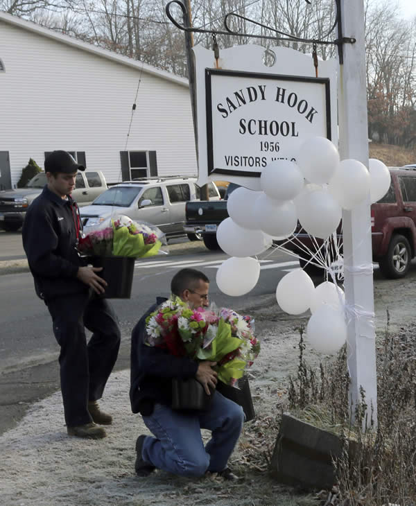 Volunteer firefighters place flowers at a makeshift memorial at a sign for the Sandy Hook Elementary school Saturday, Dec. 15, 2012 in the Sandy Hook village of Newtown, Conn. The massacre of 26 children and adults at Sandy Hook Elementary school elicited horror and soul-searching around the world even as it raised more basic questions about why the gunman, 20-year-old Adam Lanza, would have been driven to such a crime and how he chose his victims. <span class=meta>(AP Photo&#47;Mary Altaffer)</span>