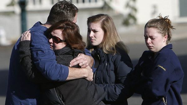 Mourners embrace outside Saint Rose of Lima Roman Catholic Church, Saturday, Dec. 15, 2012 in Newtown, Conn. The massacre of 26 children and adults at Sandy Hook Elementary school elicited horror and soul-searching around the world even as it raised more basic questions about why the gunman, 20-year-old Adam Lanza, would have been driven to such a crime and how he chose his victims <span class=meta>(AP Photo&#47;Jason DeCrow)</span>