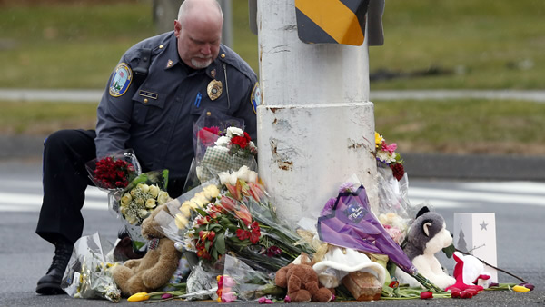 "<div class=""meta ""><span class=""caption-text "">A police officer relocates items from a memorial to shooting victims that had been left in the middle of a busy intersection, Sunday, Dec. 16, 2012 in Newtown, Conn. A gunman walked into Sandy Hook Elementary School in Newtown Friday and opened fire, killing 26 people, including 20 children. The items were taken to nearby Saint Rose of Lima Roman Catholic Church. (AP Photo/Jason DeCrow)</span></div>"