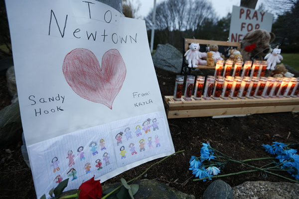 "<div class=""meta ""><span class=""caption-text "">A child's message rests with a memorial for shooting victims, Sunday, Dec. 16, 2012, in Newtown, Conn. A gunman walked into Sandy Hook Elementary School in Newtown on Friday and opened fire, killing 26 people, including 20 children. (AP Photo/Jason DeCrow)</span></div>"
