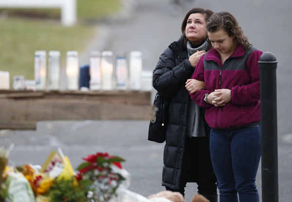 People pay respects by a makeshift memorial outside of St. Rose of Lima Roman Catholic Church between Mass services, Sunday, Dec. 16, 2012, in Newtown, Conn. On Friday, a gunman allegedly killed his mother at their home and then opened fire inside the Sandy Hook Elementary School, killing 26 people, including 20 children. (AP Photo/Julio Cortez)