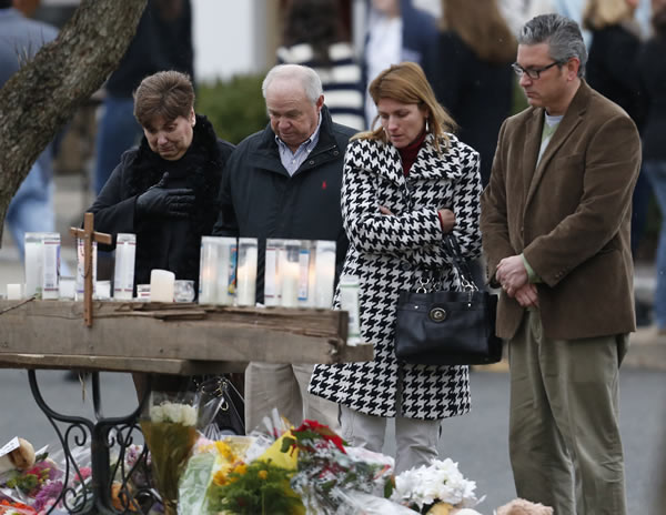 "<div class=""meta image-caption""><div class=""origin-logo origin-image ""><span></span></div><span class=""caption-text"">People pay respects at a makeshift memorial outside of St. Rose of Lima Roman Catholic Church between Mass services, Sunday, Dec. 16, 2012, in Newtown, Conn. On Friday, a gunman allegedly killed his mother at their home and then opened fire inside the Sandy Hook Elementary School in Newtown, killing 26 people, including 20 children. (AP Photo/Julio Cortez)</span></div>"