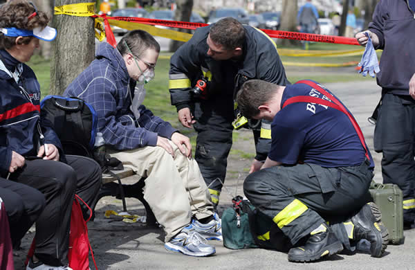 Firefighters tend to a man following an explosion at the finish line of the Boston Marathon in Boston, Monday, April 15, 2013. (AP Photo/Michael Dwyer)
