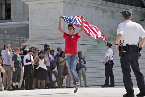 A gay rights activist runs out of the Supreme Court in Washington, Wednesday, June 26, 2013, as rulings were handed down that impact on same-sex relationships.