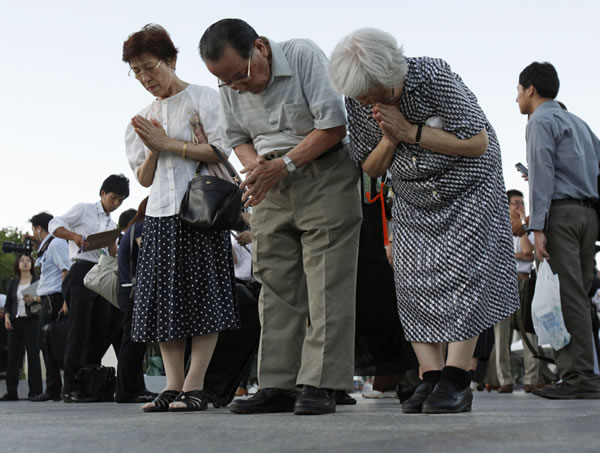 People pray for the atomic bomb victims in front of the cenotaph at the Peace Memorial Park in Hiroshima, western Japan, Friday, Aug. 6, 2010. Hiroshima marked the 65th anniversary of the the world's first atomic bomb attack that devastated the western Japanese city at the closing days of World War II. (AP Photo/Shuji Kajiyama)