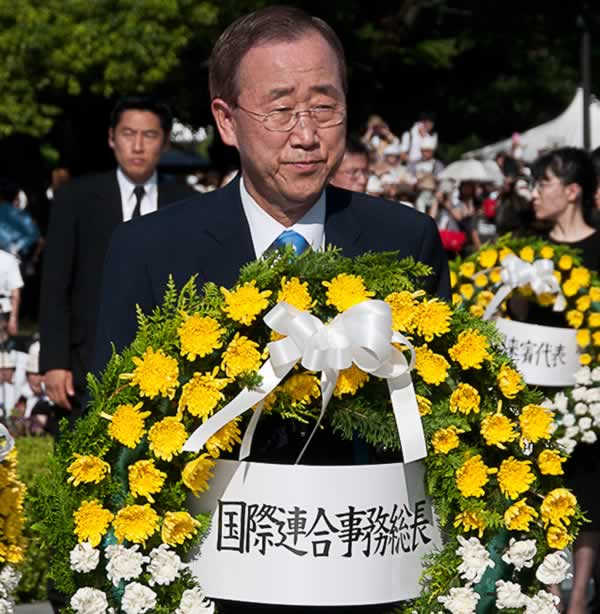 "In this photo provided by the City of Hiroshima, U.N. Secretary-General Ban Ki-moon carries the wreath to lay down at the cenotaph for the atomic bomb victims, during the 65th anniversary of the 1945 atomic bombing at the Peace Memorial Park at Hiroshima, western Japan, Friday, Aug. 6, 2010. The Japanese attached to the wreath reads "" U.N. Secretary-General."" (AP Photo/City of Hiroshima)"